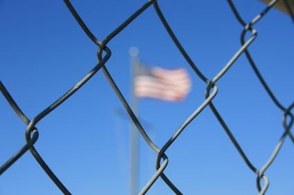 American flag through a fence