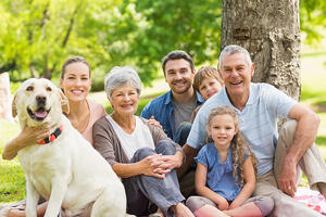 Portrait of an extended family with their pet dog sitting at the park-1